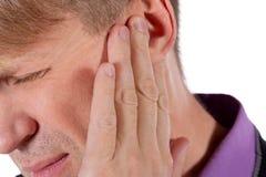 De mens heeft een pijnlijk oor Mens die aan oorpijn op witte achtergrond lijden royalty-vrije stock foto