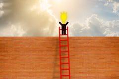 De mens heeft idee die zich bovenop ladder over bakstenen muur bevinden Royalty-vrije Stock Afbeeldingen