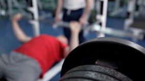 De mens heft vrij gewicht onder controle van instructeur in sportclub op De knappe kerel ligt op bank en oefent uit met stock videobeelden