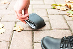 De mens heft zijn zwarte portefeuille met geld op de straat op Stock Foto