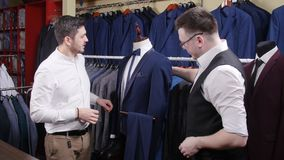 De mens helpt een andere poging op een kostuum in een kledingsopslag stock videobeelden