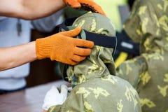 De mens helpt om op paintballmasker voor een jongen te zetten Paintballspel stock foto's