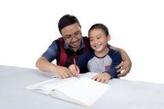 De mens helpt zijn zoon die thuiswerk doen Royalty-vrije Stock Afbeeldingen