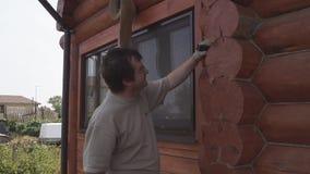 De mens herstelt een blokhuis stock video