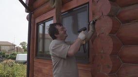 De mens herstelt een blokhuis stock footage