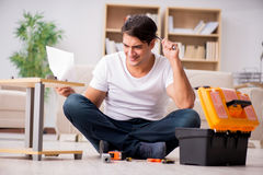De mens het assembleren plank thuis stock foto's