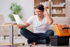 De mens het assembleren plank thuis stock fotografie