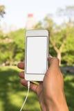 De mens is het luisteren mobiele telefoon in het park Royalty-vrije Stock Afbeeldingen