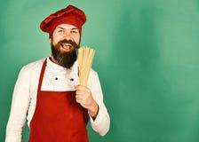 De mens of hipster met baard houdt macaroni op groene achtergrond stock afbeelding