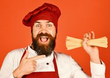De mens of hipster met baard houdt macaroni op rode achtergrond royalty-vrije stock fotografie