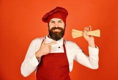De mens of hipster met baard houdt macaroni op rode achtergrond stock afbeeldingen