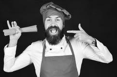 De mens of hipster met baard houdt macaroni op zwarte achtergrond Chef-kok met bos van spaghetti Kok met vrolijk gezicht stock fotografie