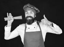 De mens of hipster met baard houdt macaroni op zwarte achtergrond De chef-kok met spaghetti toont duimen Kokend Italiaans voedsel stock foto's