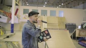 De mens in hoed, jeansjasje spreekt in microfoon aan mensen in skatepark uitdaging competition gastheer stock footage