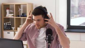 De mens in hoofdtelefoons met laptop spreekt aan microfoon stock video