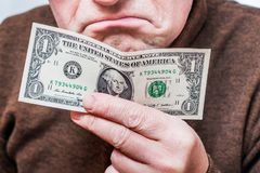 De mens houdt één dollar in zijn hand en drukt ongenoegen bij uit royalty-vrije stock foto
