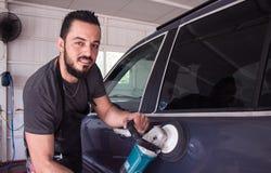 De mens houdt auto oppoetsend hulpmiddel in de handen en de glimlach Stock Foto's