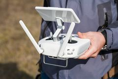 De mens houdt een hommel ver controlemechanisme in zijn handen Close-up van quadrocopter RC tijdens vlucht Proef neemt luchtfoto' stock foto