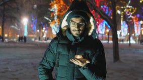 De mens houdt een lamp met een kaars in een sneeuwval in het park in hand stock videobeelden
