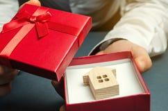 De mens houdt een miniatuurhuis in een giftdoos Het huisvesten als gift Win een flat in de loterij Om bezit te erven vakantie stock foto