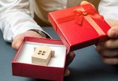 De mens houdt een miniatuurhuis in een giftdoos Het huisvesten als gift Win een flat in de loterij Om bezit te erven vakantie stock foto's