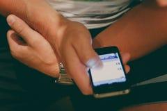 De mens houdt een smartphone in zijn hand en let op een nieuwslijn royalty-vrije stock foto