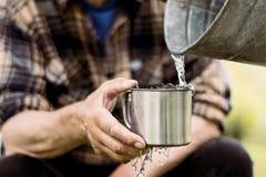 De mens houdt een staalmok en een bronwater giet van een emmer stock fotografie