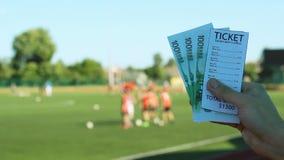 De mens houdt een van het bookmaker` s kaartje en geld euro op de achtergrond van een spel van de stadionvoetbal, close-up stock footage