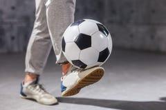 De mens houdt een voetbalbal op zijn been royalty-vrije stock afbeeldingen