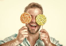 De mens houdt grote lollys op ogen als oogglazen De mens met varkenshaar houdt van snoepjes Zoet tandconcept Kerel op het glimlac stock afbeelding