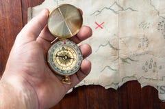 De mens houdt het kompas boven valse piraatkaart van abstract eiland met rood kruis van plaats waar schat is Stock Foto