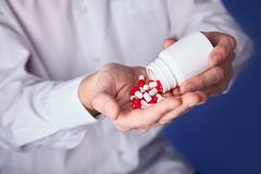 De mens houdt multi-colored pillen in handen De panacee, het leven sparen de dienst, schrijft geneesmiddel, wettelijke drogisteri royalty-vrije stock foto