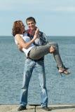 De mens houdt in openlucht zijn vrouw op handen Stock Fotografie