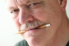 De mens houdt potlood in mond Stock Foto's
