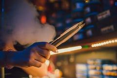 De mens houdt roodgloeiende steenkool met tang, waterpijp het roken royalty-vrije stock foto's