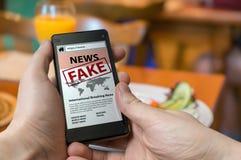 De mens houdt smartphone en leest vals nieuws op Internet Propaganda, desinformatie en hoax concept stock afbeelding