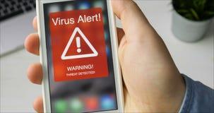 De mens houdt smartphone met virus waakzaam waarschuwingsbord op de vertoning
