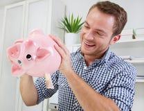 De mens houdt spaarvarken Royalty-vrije Stock Afbeeldingen