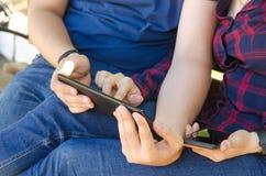 De mens houdt tablet in zijn handen en de meisjeszitting naast leidt de tablet stock afbeelding