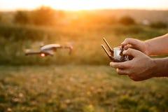 De mens houdt ver controlemechanisme met zijn handen terwijl de helikopter op achtergrond vliegt De hommel hangt achter de loods  stock foto