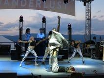 De mens houdt verpakte persoon met benen aangezien de mensen rond hem du dansen Royalty-vrije Stock Afbeeldingen