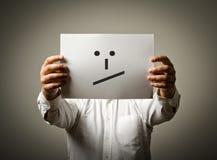 De mens houdt Witboek met glimlach Onbeslist concept Stock Afbeeldingen