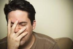 De mens houdt zijn gezicht in pijn Stock Foto