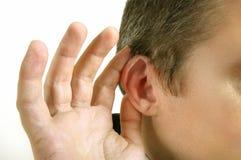 De mens houdt zijn hand dichtbij zijn oor en het luisteren iets Royalty-vrije Stock Afbeelding