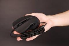 De mens houdt in zijn optische muis van de hand zwarte computer Stock Afbeeldingen