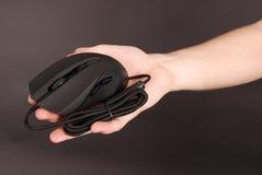 De mens houdt in zijn optische muis van de hand zwarte computer Royalty-vrije Stock Afbeelding