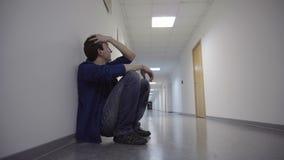 De mens hurkt in de lange witte gang, die tegen de muur leunen, biddend, hopend en wacht stock video