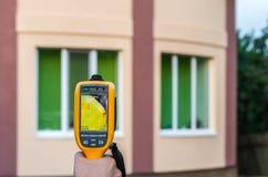 De mens inspecteert huis met thermische weergavecamera Stock Foto