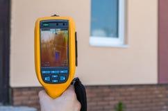 De mens inspecteert huisvenster met thermische weergavecamera Stock Fotografie