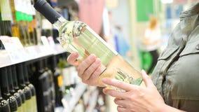 De mens kiest alcoholische dranken op de teller van alcoholische afdelingssupermarkt slow-motion 4k, stock footage